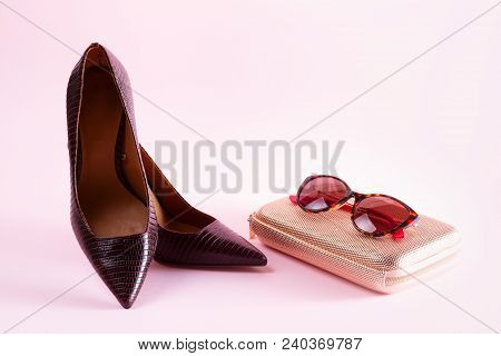 Pair Of Elegant Leather High Heel Shoes With Bag And Sunglasses On Pink Background
