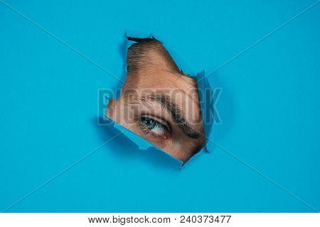 Eye Looking Through Hole In Paper. Spy Eye Watching Through A Hole. Eye Looking Through Hole In Blue