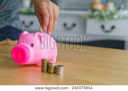 Woman Putting Coin In Piggy Bank And Stack Of Coins Beside. Concept Of Property.