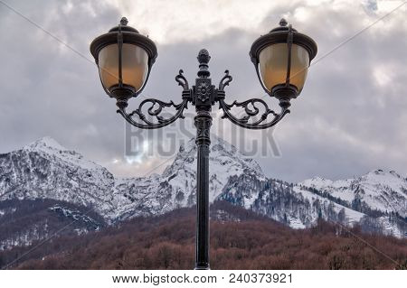 Streetlight On The Background Of Mountain Covered With Snow In Winter Day Closeup, Krasnaya Polyana,