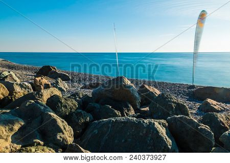 Long-exposure View Of The Sea And Sails For Windsurfing On The Rocky Beach In Sunny Day