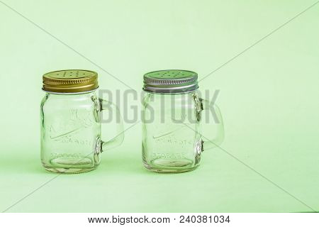 Empty Salt, Pepper Shakers On Green Background