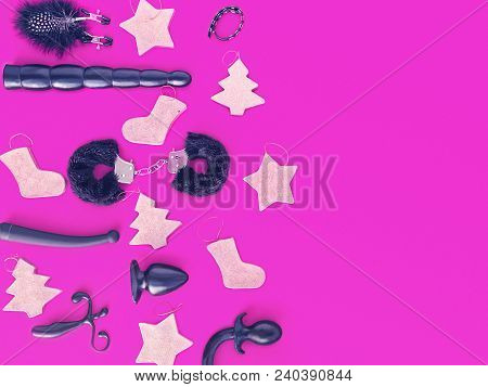 Various Sex Toys (whip, Dildo, Handcuffs, Vibrator And Other) And Paper Christmas Toys Are On A Purp