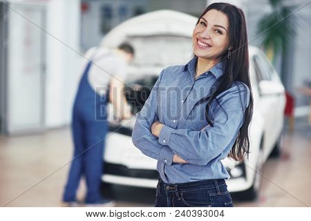 Woman At A Car Garage Getting Mechanical Service. The Mechanic Works Under The Hood Of The Car.