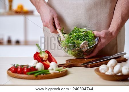 Man Cooking At Kitchen Making Healthy Vegetable Salad, Close-up, Selective Focus. Variety Of Vegetab