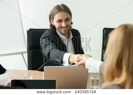 Smiling Businessman In Suit Handshaking Greeting Businesswoman At Group Negotiation, Friendly Succes