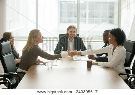 Diverse Smiling Businesswomen Shaking Hands Greeting At Multiracial Group Meeting, Friendly African