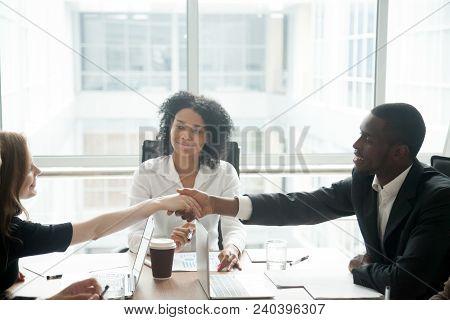 Smiling African Businessman Handshaking Greeting Caucasian Businesswoman At Group Meeting Negotiatio
