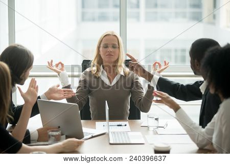 Female Boss Calming Down Meditating At Stressful Office Meeting, Peaceful Mindful Businesswoman Prac