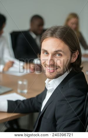 Smiling Young Businessman In Suit Looking At Camera At Meeting, Head Shot Portrait Of Successful Exe