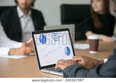 Black Project Manager Working On Computer Analyzing Statistics On Screen At Multiracial Meeting, Afr