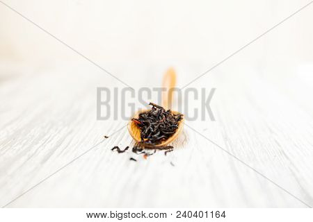 Composition of natural black tea with a leaves of rose. Macro photo of tea petals on a wooden spoon
