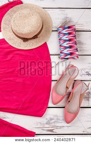 Female Clothes And Accessories, Wooden Background. Women Shirt, Hat, Sandals And Toiletry Bag. Femin