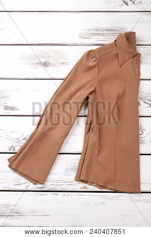 Female Shirt Folded On Wooden Background. Women New Blouse With Long Sleeves On Wooden Table. Female