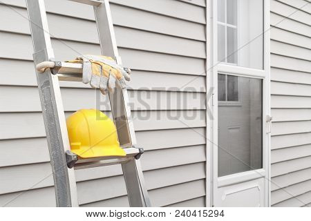 Yellow Hard Hat And Work Gloves On Ladder With House Siding Background.