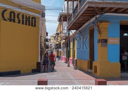 Santa Marta, Columbia-- April 22, 2018. Photo Of Pedestrians On A Brightly Colored Side Street In Sa