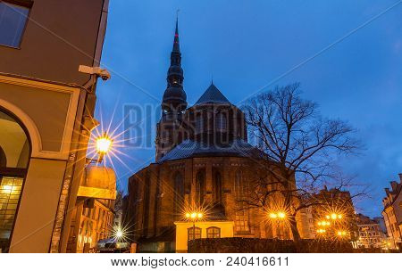 The St. John's Church And Spire Of Cathedral Of St. Peter At Night, Riga, Latvia