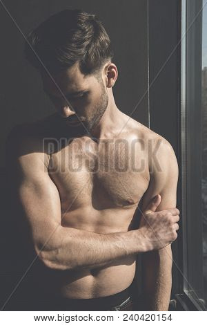 Masculinity and sensuality. Shirtless young stylish thoughtful man is demonstrating his perfect body while posing near window. Sunshine on his torso poster