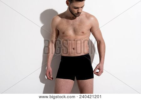 Youn Shirtless Healthy Athletic Man Is Standing Against Light Background. He Is Posing Wearing Boxer