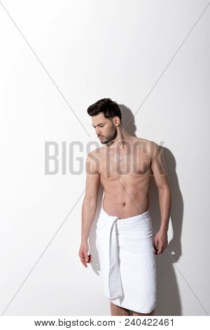 Manliness. Young Attractive Topless Man With Beard Is Standing Against White Wall With Towel On His
