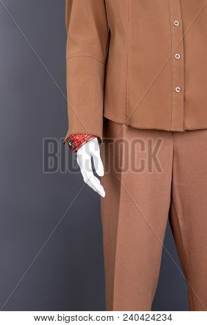 Mannequin With Red Bracelet On Hand. Female Brown Garment On Mannequin, Cropped Image. Ladies Formal