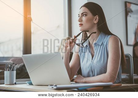 Portrait Of Thoughtful Female Working With Notebook Computer In Office. Contemplative Lady During La
