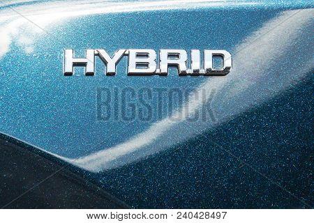 Close-up Side View Of Modern Hybrid Car. Hybrid  Symbol On Metallic Shiny Car Fender. Green Eco Ener