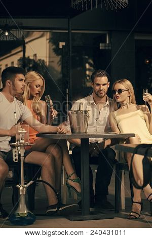 Friends Vapor Hookah And Drink Alcohol In Bar Lounge. Twins Women And Men Relax In Shisha Cafe Outdo