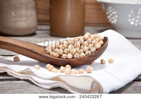 Dry Chickpeas In A Wooden Spoon. Also Called Garbanzo Beans.