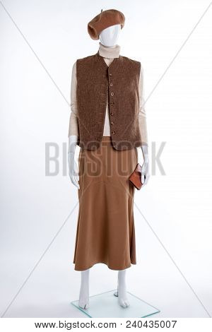 Brown Beret, Waistcoat And Skirt. Female Mannequin Dressed In Vest And Skirt, White Background. Fema