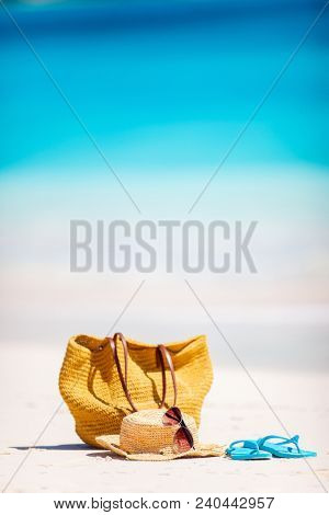 Straw bag, sun glasses, towel and flip flops on a tropical beach