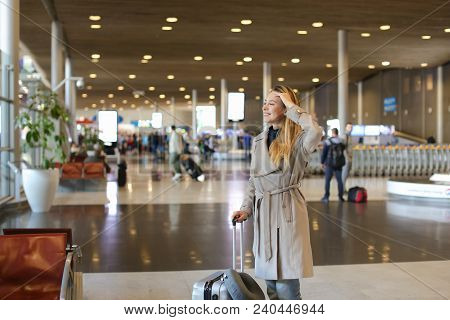Caucasian Girl Walking In Airport Waiting Room With Valise And Neck Pillow. Concept Of Traveling Abr