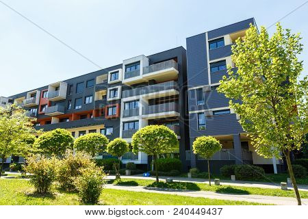 Exterior Of A Modern Black Apartment Buildings On A Blue Sky Background. No People.  Real Estate Bus