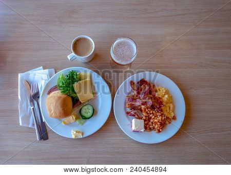 Two Breakfast Plates With Eg Bred, Bacon And Scrambled Eggs, And Coffee With Milk And Apple Juice