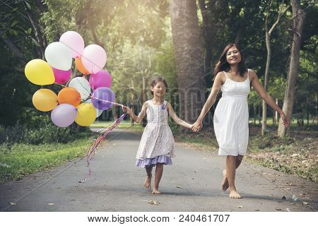 Adorable Cute Girl Holding Balloons With Mother Walking On The Road In The Park