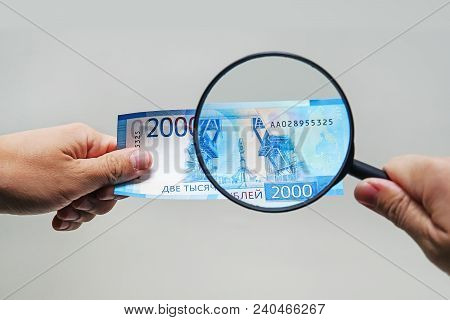 Expert With Magnifying Glass Checks Suspicious Money. Search Watermarks On Paper Of The Fake Bills.
