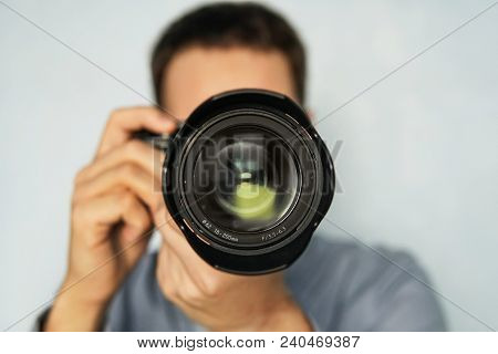 The Man Use The Professional Camera With Telephoto Lens. Close Up Photo Of Man In Hat On Blue Backgr