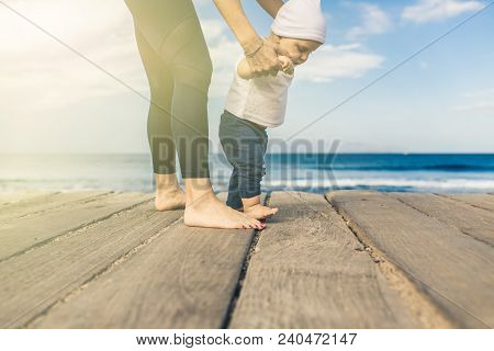 Baby Boy Walking On The Beach In Beautiful Summer Day. Mother With Toddler Son Learning To Walk On W
