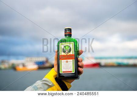 Reykjavik, Iceland - October 13, 2017: Bottle Of Jagermeister In Hand On Seascape. Alcohol Drink Wit