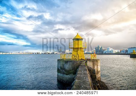 Lighthouse Tower On Stone Pier In Reykjavik, Iceland. Lighthouse In Sea. Seascape And Skyline On Clo
