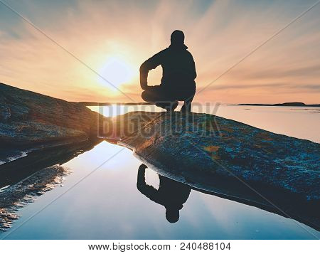 Lonely Man Hiker Sits Alone On The Rocky  Coast And  Enjoying Sunset. View Over Rocky Cliff To Free