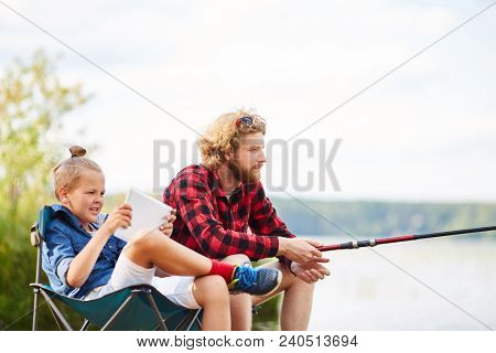 Young restful man rodding by lake with his son sitting near by and watching online video in touchpad