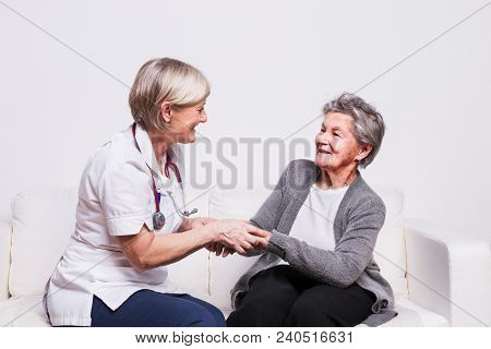 Studio Portrait Of A Senior Nurse And An Elderly Patient. Two Women Talking, Holding Hands.