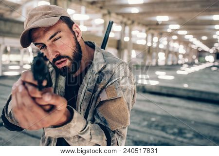 Guy Is Taking Aim. He Is Looking Straight Forward On Camera. He Wears Military Uniform. Man Is Serio
