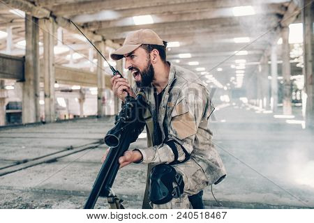 A Picture Of Emotional And Adult Soldier Screaming In Portable Radio. He Is Holding It In Right Hand