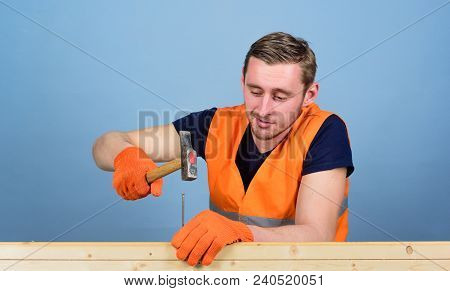 Handyman Concept. Man, Handyman In Working Uniform And Protective Gloves Handcrafting With Hammer, L