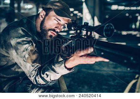 Portrait Of Brunette Is Taking Aim. He Is Looking Through Lens. Guy Is Holding Rifle With Right Hand
