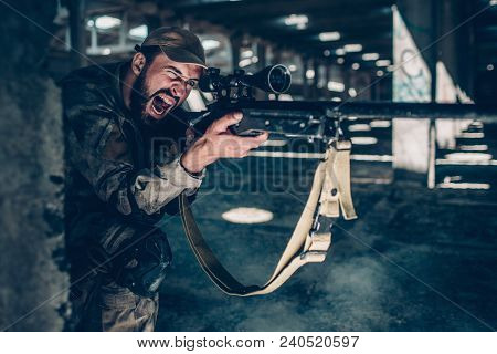 Horizontal Picture Of Soldier Is Sitting On The Ground On One Knee Near Column And Screaming. He Is