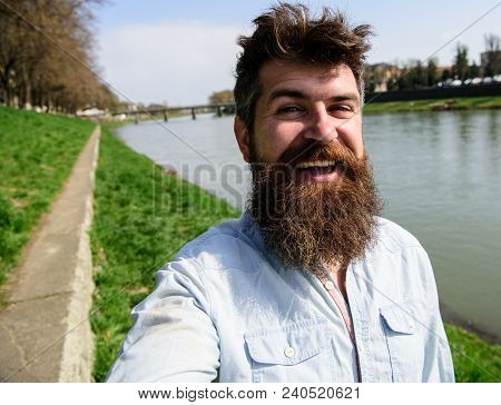 Man, Tourist With Beard And Mustache On Cheerful, Smiling Face, Riverside Background. Selfie Photo C