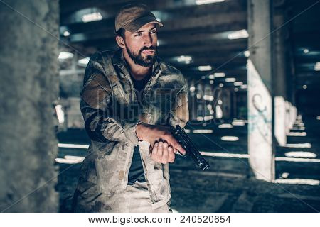 Calm Fighter Wears Military Uniform. He Is Standing Besides Column And Paying Good Attention. He Is